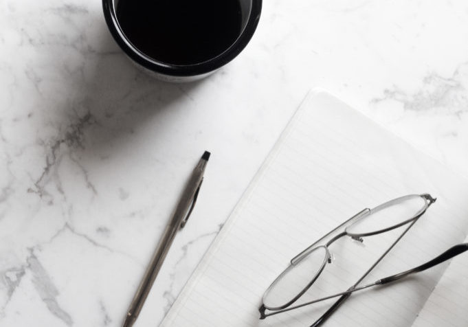 a photo from above of a cup of coffee, pen, paper and glasses on a white marble table
